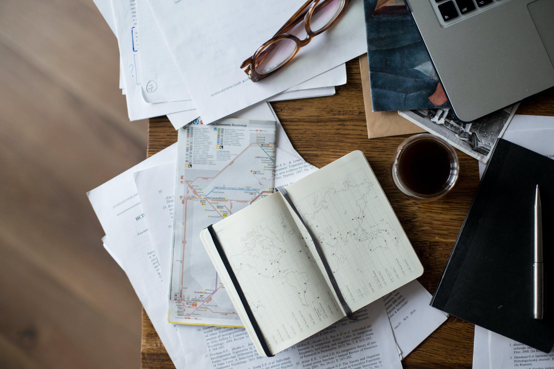 brown framed eyeglasses on white printer paper beside white ceramic mug